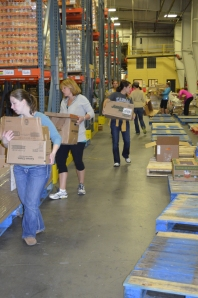 Prospective Members help organize food at Harvesters.