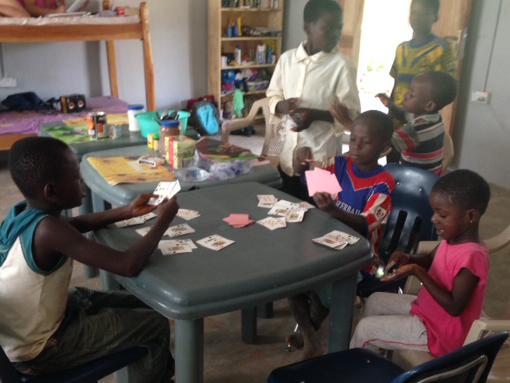 Local children playing cards in the volunteer house